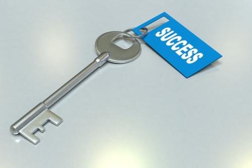 Afbeelding van een sleutel met een blauw label waarop succes staat.