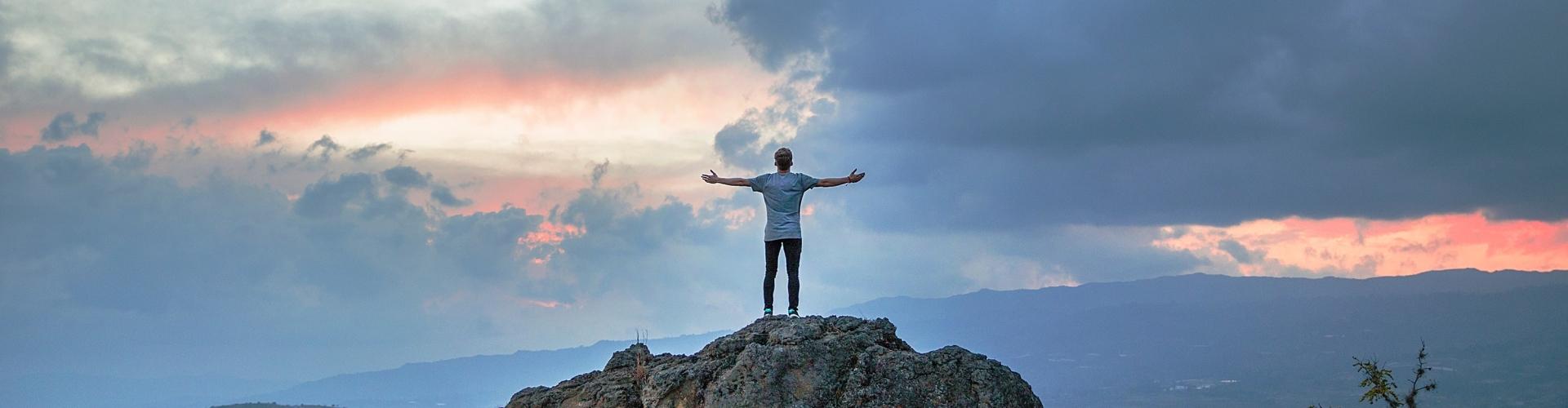Man op rots met armen in de lucht
