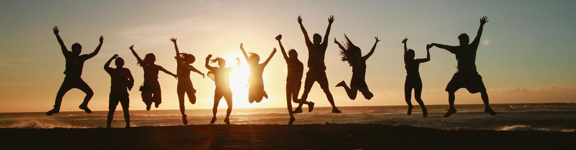 Groep van 11 mensen juichen bij zonsondergang