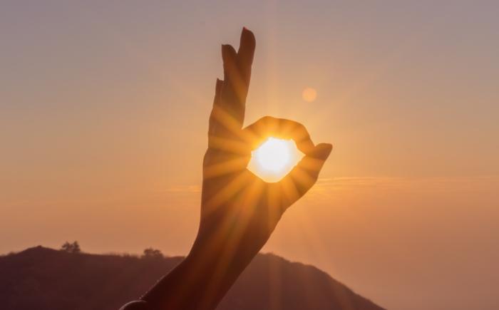Hand in de zon tussen wijsvinger en duim