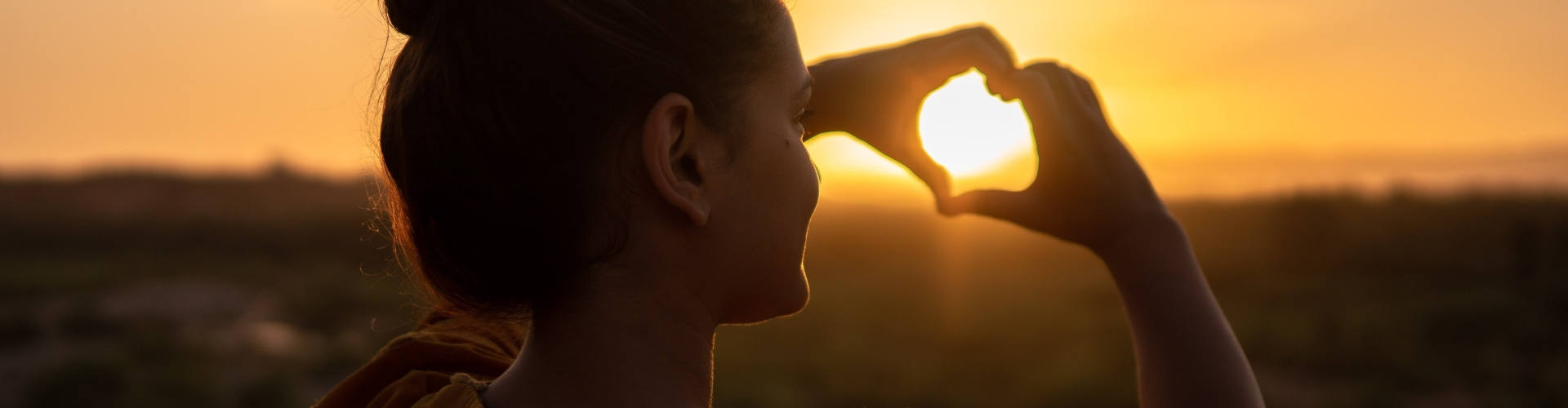 Vrouw houd hand in de vorm van hartje naar de zon