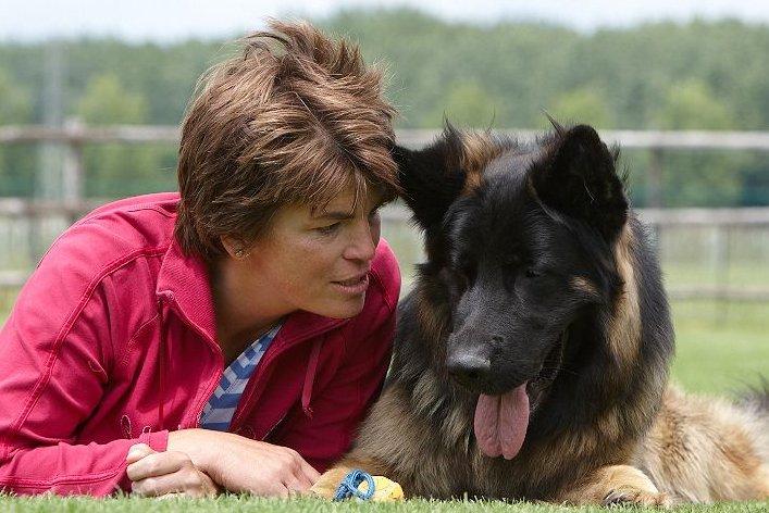 Mandy ligt met Herder Wilson samen in het gras