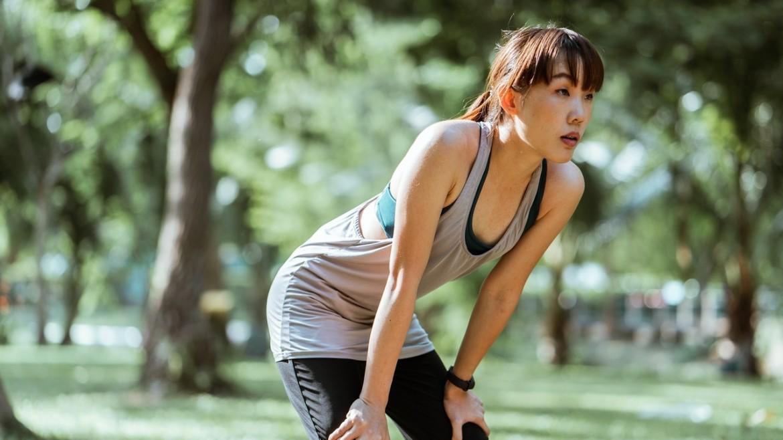 Vrouw rust uit van hardlopen omdat ze een hoge en snelle ademhaling heeft
