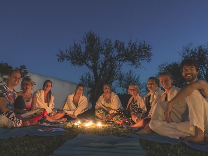 Deelnemers van de transformatiereis (yogaretreat met coaching) in Portugal zitten in een kring voor de avondceremonie