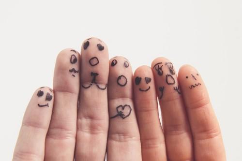 Getekende gezichten op vingertoppen met verschillende uitdrukkingen van emoties, angsten en beperkende overtuigingen