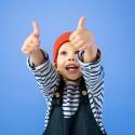 Jongetje steekt 2 duimen in de lucht en kijkt happy en blij en voelt zicht goed