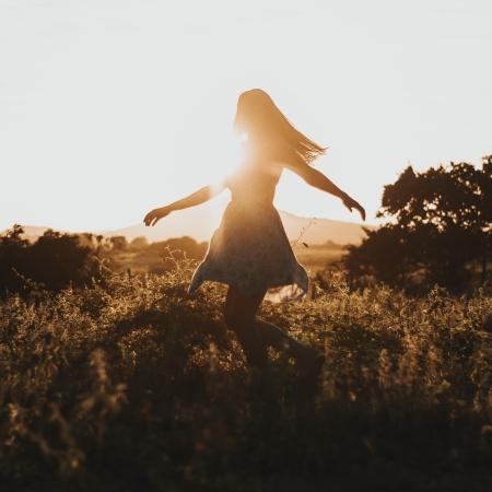Vrouw dansend in de ochtendzon in de natuur