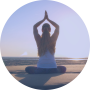 Vrouw op het strand zit met handen boven haar hoofd in namaste en heeft innerlijke rust en een rustige geest