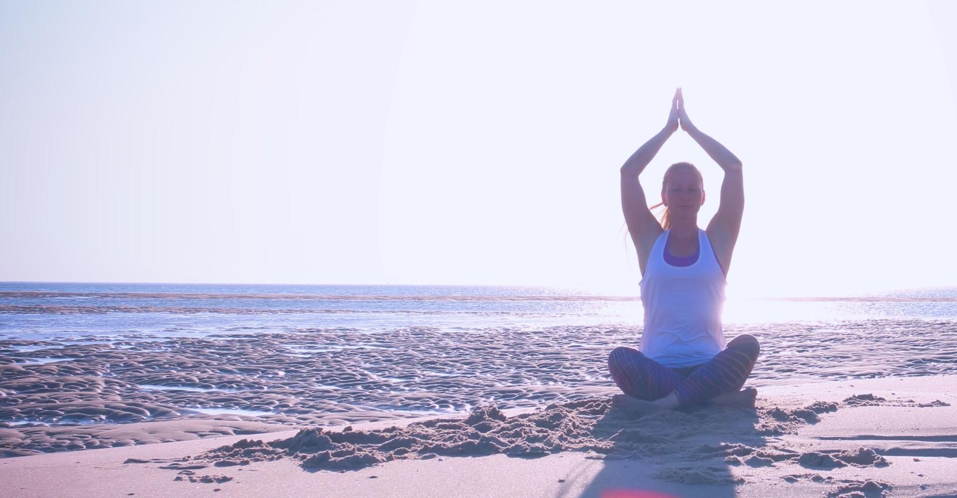 Vrouw op het strand met handen boven het hoofd voelt innerlijke rust en ontdekt haar superpowers