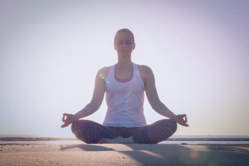 Marjolein Groen in meditatiehouding op het strand