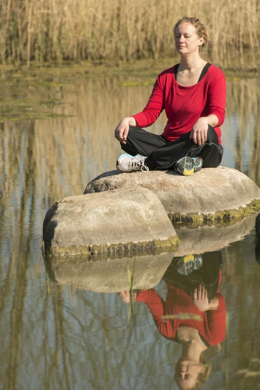 Vrouw op rost in het water mediteert en ervaart innerlijke rust