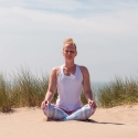 Vrouw mediteert op het strand, even stilstaan en me-time