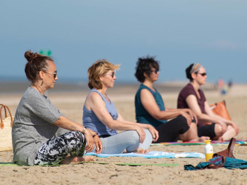 Drie deelnemers mediteren op het strand tijdens yogales