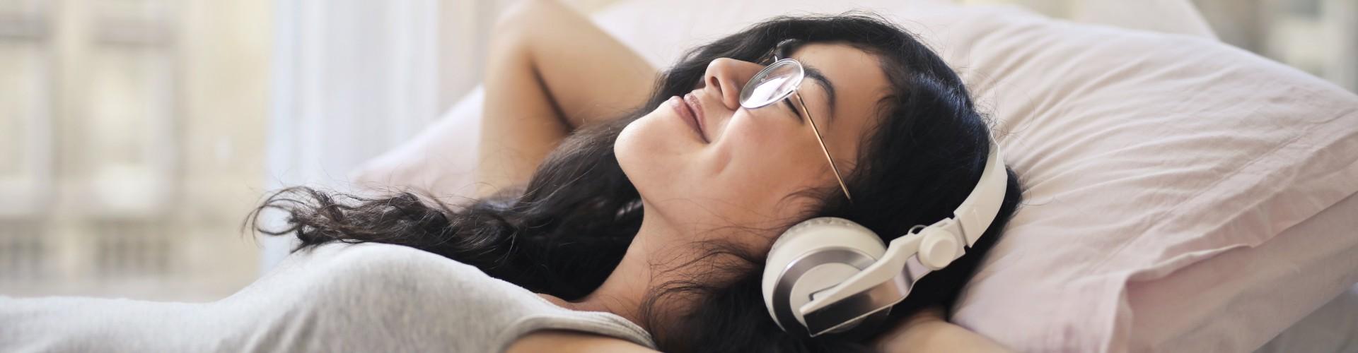 Vrouw in wit shirt ligt met headphone ontspannen te luisteren naar meditatie-, adem- en hypnose oefeningen
