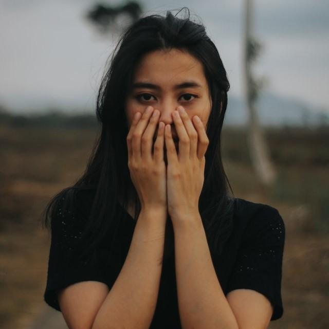 Vrouw met onzekerheid en (faal)angst houdt haar handen voor haar gezicht