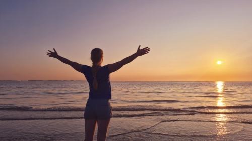 Vrouw heeft armen gespreid en opent zich voor vrijheid en transformatie