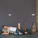 Vrouw doet restorative yoga houding liggende buiktwist