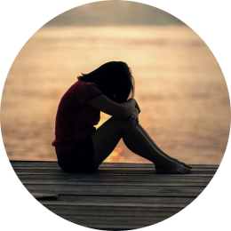 Vrouw heeft stress, angst of onzekerheid en zit aan de waterkant ineengedoken