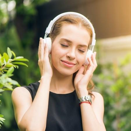Vrouw met koptelefoon voelt zich rustig en zelfverzekerd door het beluisteren van meditatie, hypnose en meer