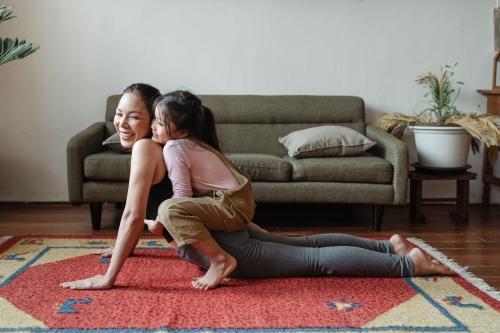 Moeder en kind doen thuis yoga in hun vertrouwde omgeving