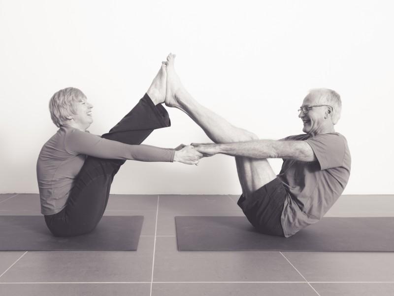 Man en vrouw op leeftijd doen een duo yogahouding, de boothouding