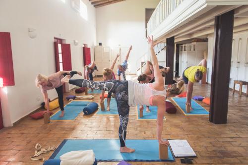 Yogadocente doet voor de klas Yogahouding Halve Maan - Ardha Chandrasana