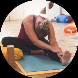 Vrouw doet Yogahouding Janu Sirsasana a hoofd naar knie houding met ondersteuning van de bolster onder haar gebogen knie