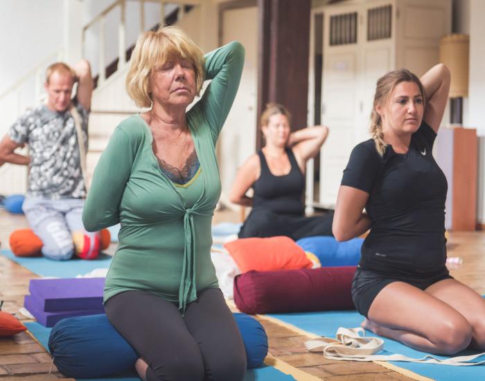Deelnemers aan yogales in Brielle doen yogahouding - Koeienkop - Gomukhasana - voor minder stress en meer innerlijke rust