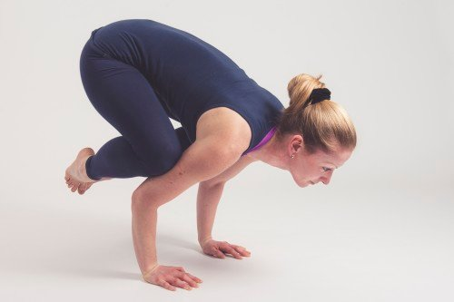 Vrouw doet yogahouding - kraai - kakasana - kraanvogel - bakasana