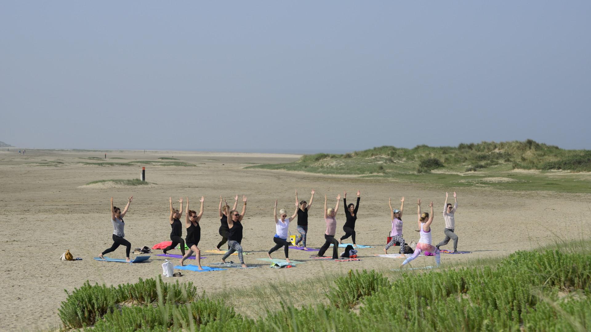 Groep yoga op Oostvoorne strand in yogahouding  krijger 1 - heldenhouding I - virabhadrasana I