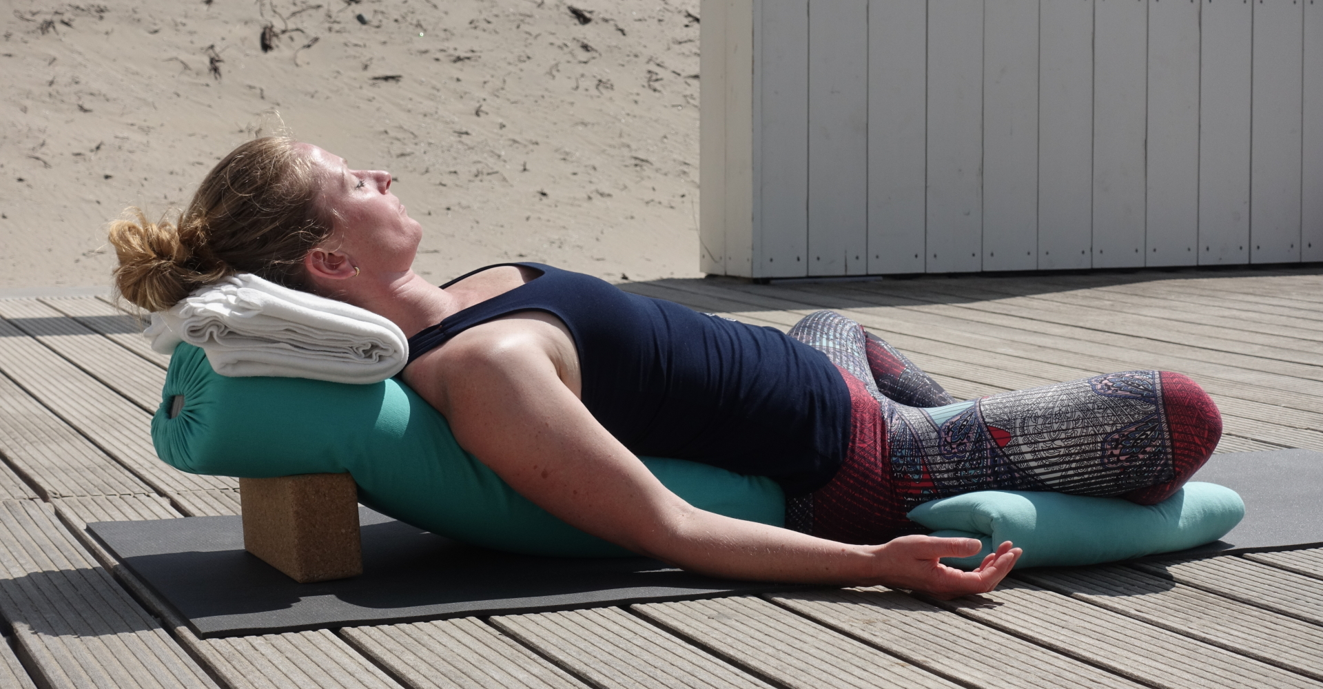 Vrouw doet yogahouding - Liggende Vlinder - Supta Baddha Konasana - restorative yoga variatie