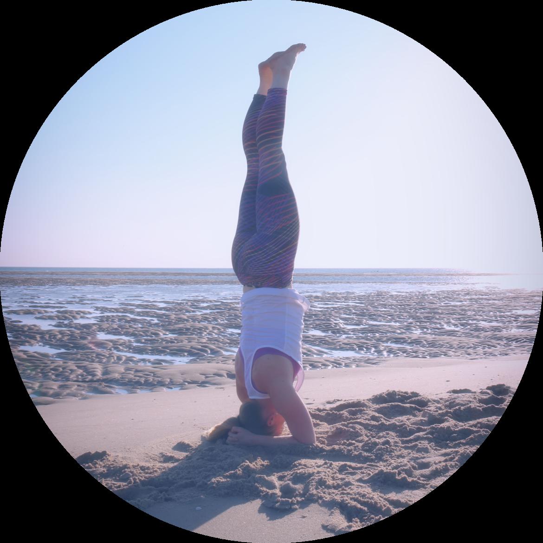 Vrouw doet hoofdstand op het strand; een houding van kracht en balans