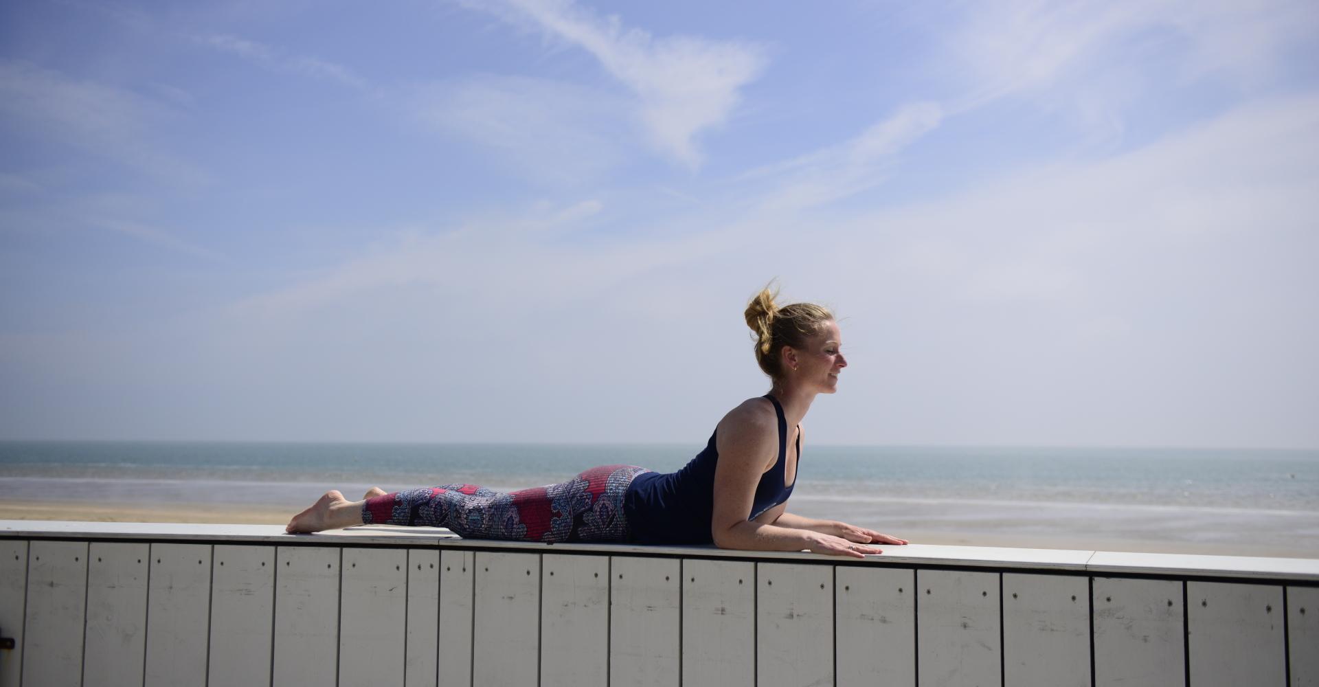 Marjolein doet yogahouding Sphinx - Salamba Bhujangasana op het strand