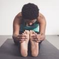 Vrouw doet yogahouding - zittende vooroverbuiging - tanghouding - paschimottanasana