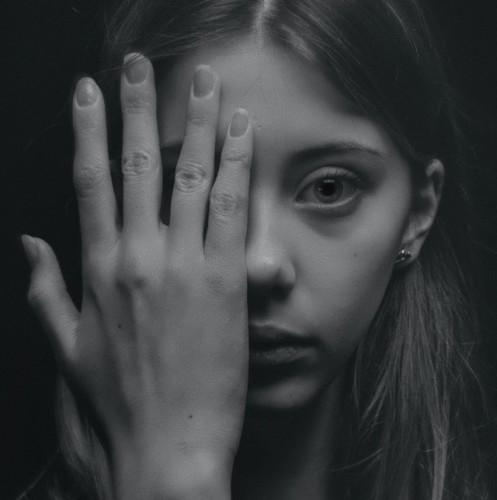 Zelfafwijzing door vrouw, bedekt de helft van aar gezicht met haar hand