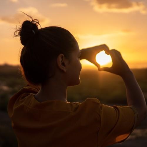 Vrouw met zelfliefde doet hartje met haar handen