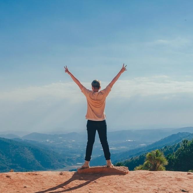 Vrouw met zelfvertrouwen en voelt zich krachtig met armen omhoog op een klif