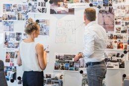 twee teamleden die brainstormen over kantoor inrichting