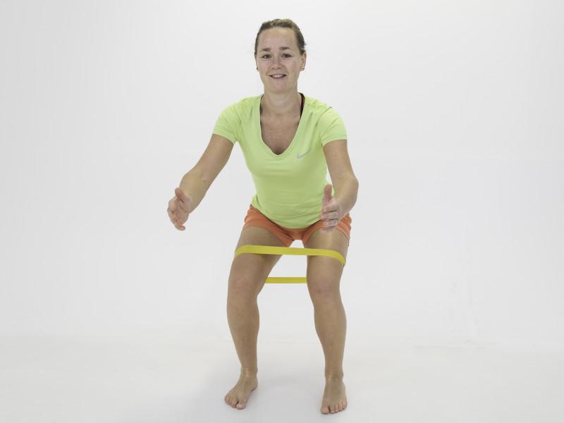 Fysio Maaike doet squat met weerstandsband