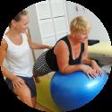 Fitbal met patiënt in fysiotherapie praktijk