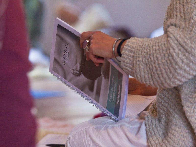 A student reading the manual of the Kundalini Yoga Coach level 1- International training