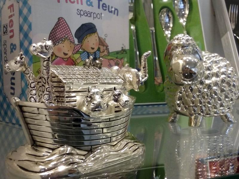 Kraamcadeau's voor jongen en meisje. Complete bestekset, bord en beker. Spaarpot, rammelaar, tand- en haardoosje. Borstel en kam. Babyarmband, zilver en goud.