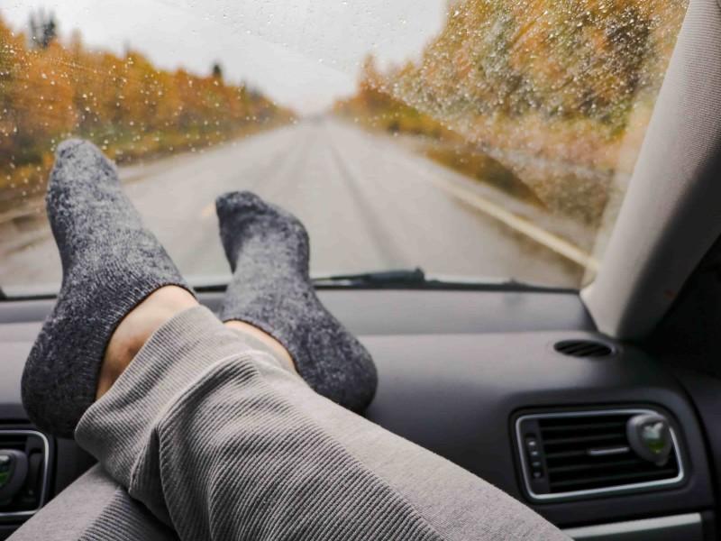 Voeten met sokken op dashboard tijdens autorit