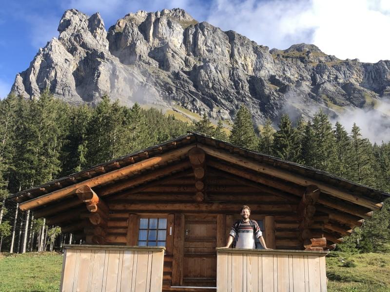 Bas Dijkstra in Zwitserse hut met bergen op de achtergrond