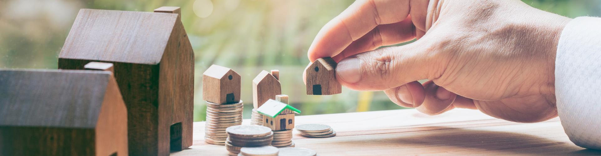 Vastgoed investeren hand met huisjes en muntstukken huisje