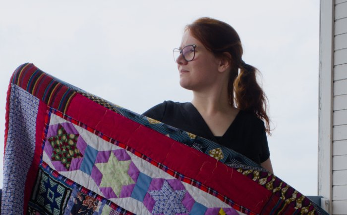 Rianne holds her kenyan quilt made with scrap fabrics and kitenge with quilt patterns designed by Rianne