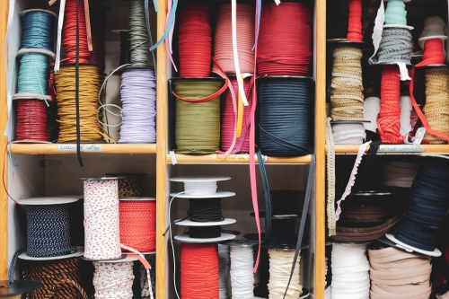 Colourful sewing and quilting thread sorted in boxes