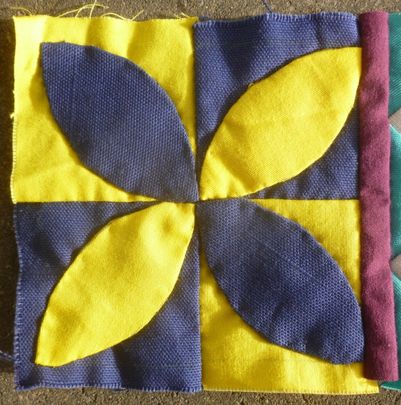 Dear Jane sampler quilt block with yellow and dark blue and a purple border made with the needle turn applique technique