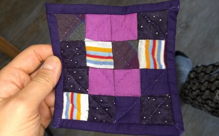Finished coaster nine patch quilt with border made with several different purple fabrics