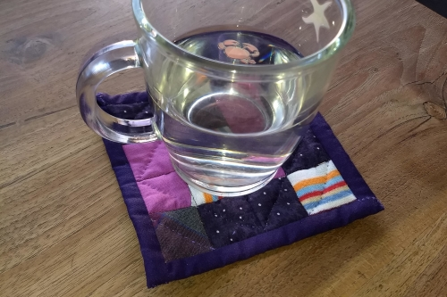 Mini quilter coaster purple with a cup of water on it. Made with the n*patch desire technique